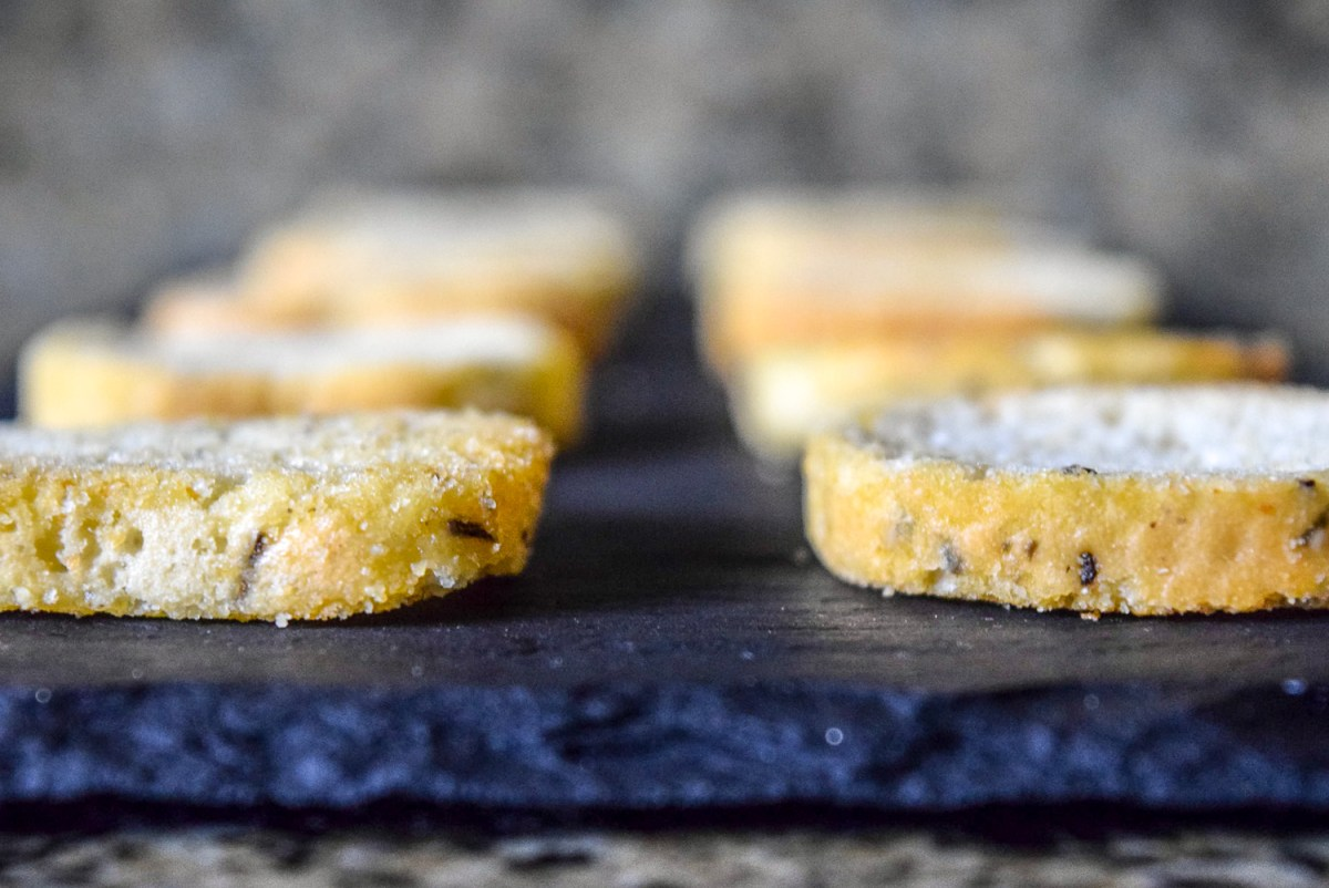 Asturi Rosemary and Olive Oil Bruchettini bread slices laid out on slate cheeseboard from front