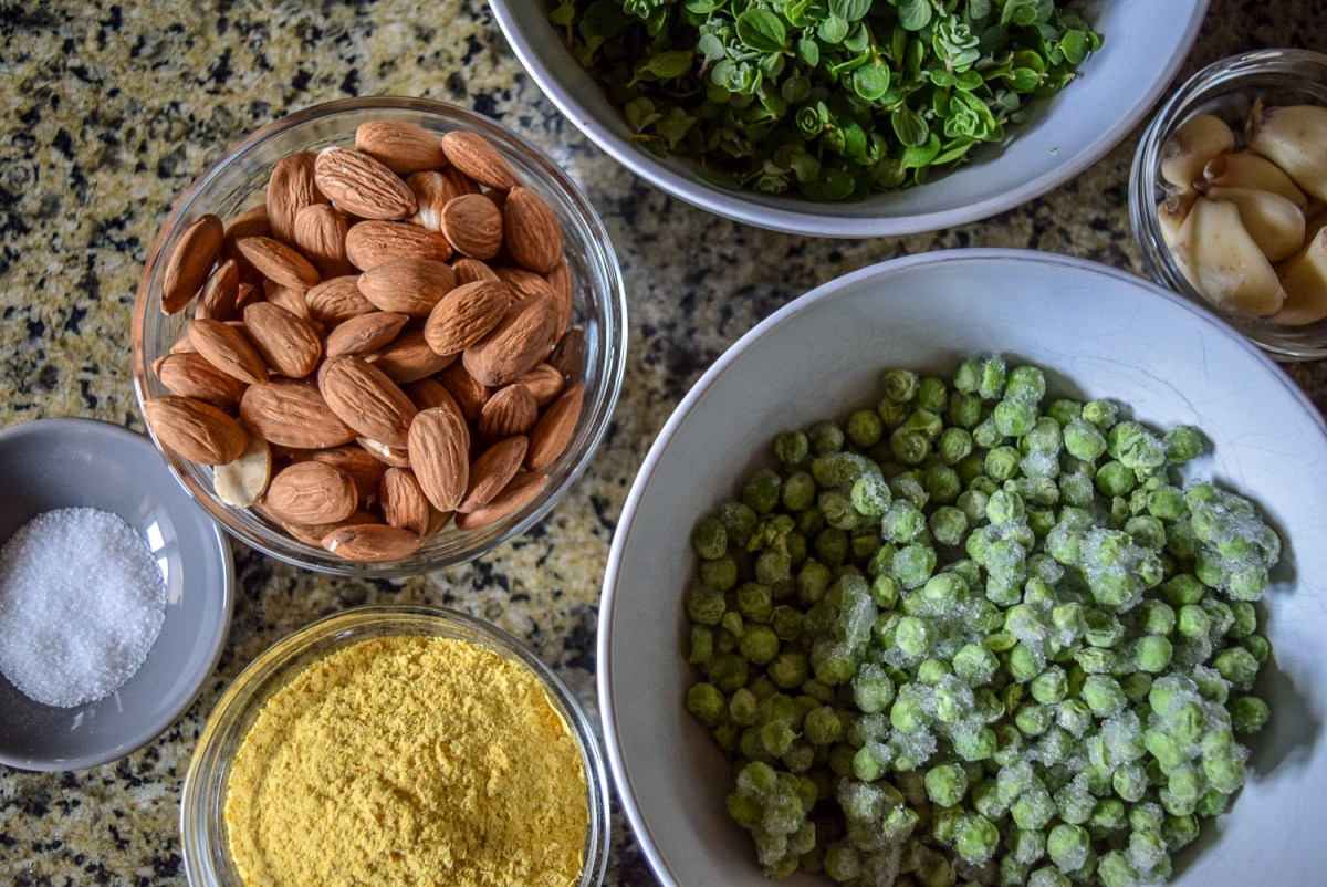 Ingredients for Vegan Marjoram Pea Pesto from top, including homegrown freshly-picked destemmed marjoram herb, frozen peas, almonds, garlic cloves, salt, and nutritional yeast