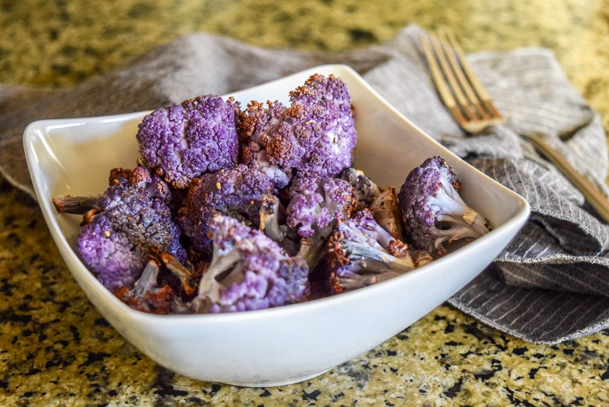 Finished roasted purple cauliflower florets from side angle with fork in background