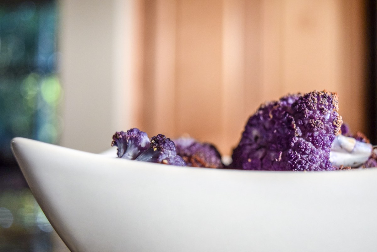 Finished roasted purple cauliflower florets up close from side