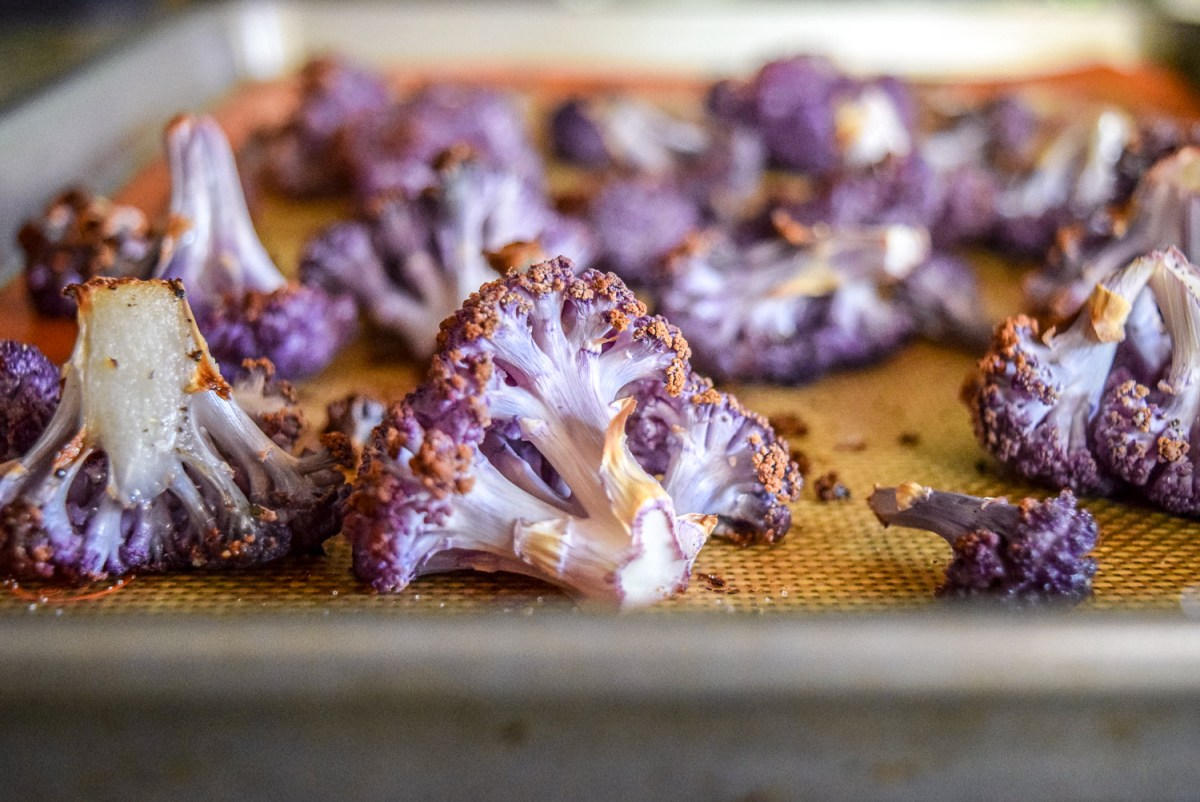 Roasted purple cauliflower florets and stem pieces on silicone baking sheet on calphalon baking sheet up close