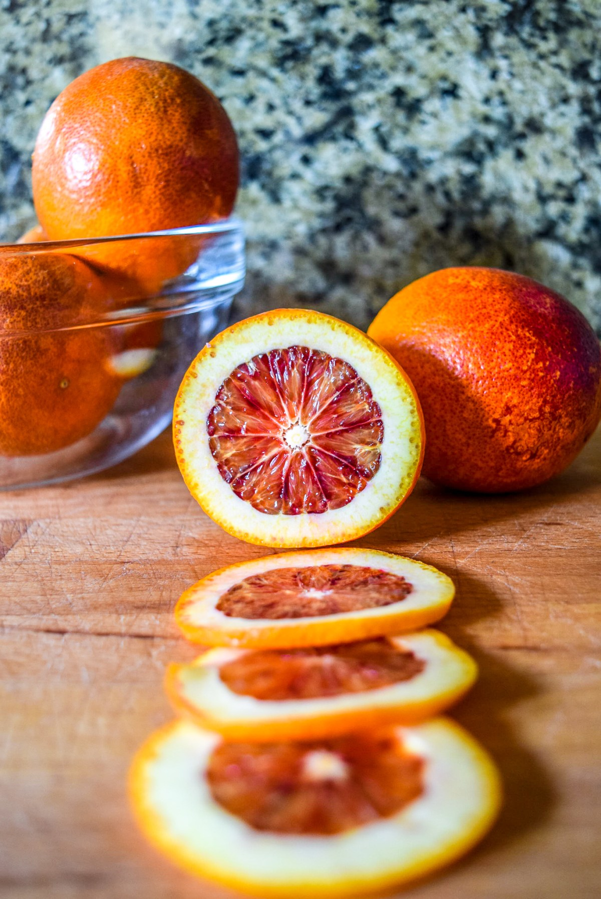 Sliced blood orange rounds in preparation for candying from front