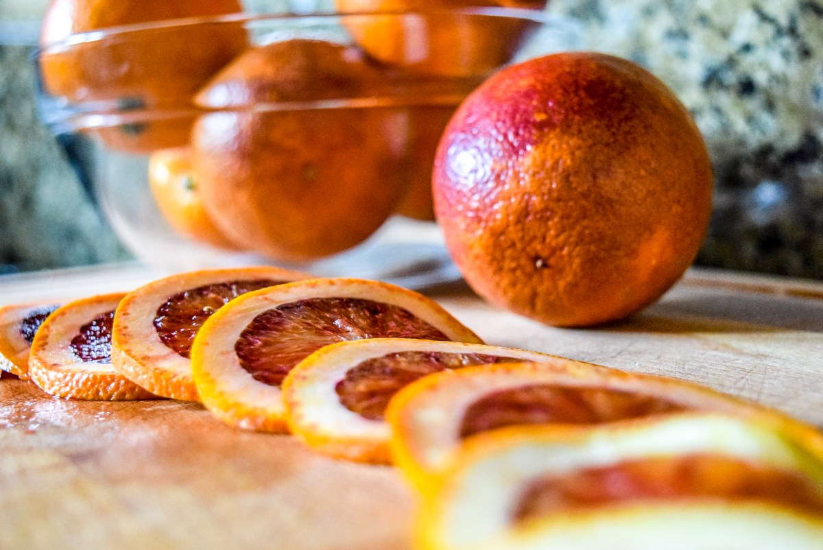 Sliced blood orange rounds in preparation for candying from front up close