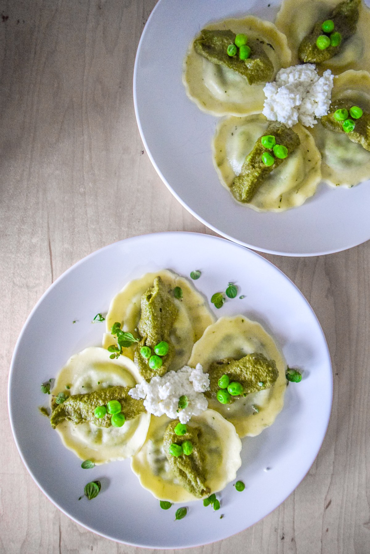 Marjoram Pea Pesto Ricotta Ravioli on two plates from top vertical