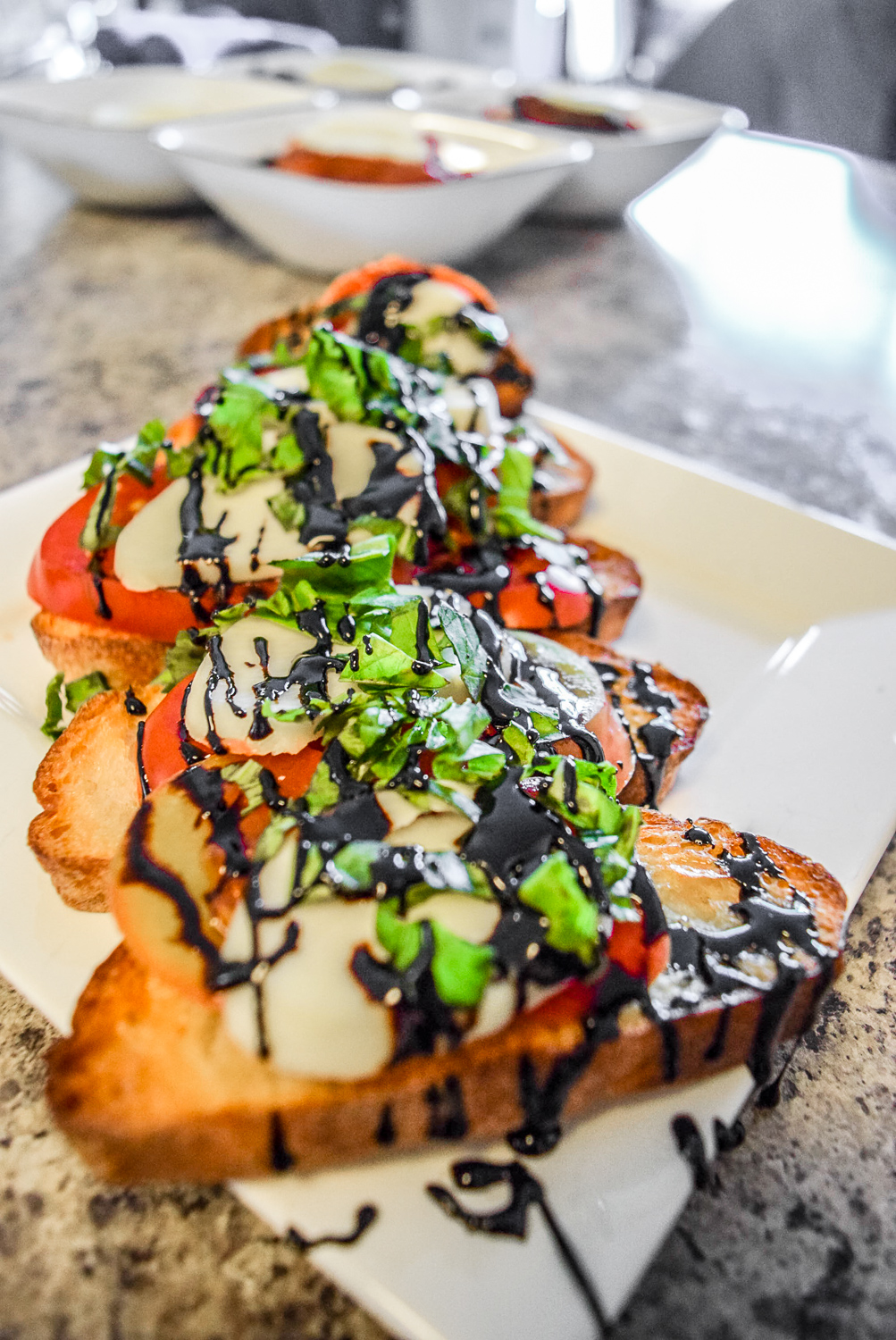 Finished caprese bruschetta with heirloom tomato, fresh basil, homemade mozzerella, and balsamic reduction from angle