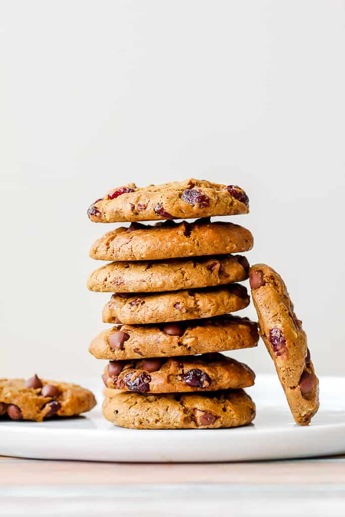 straight on shot of a stack of the pecan cranberry chocolate chip cookies on a white plate