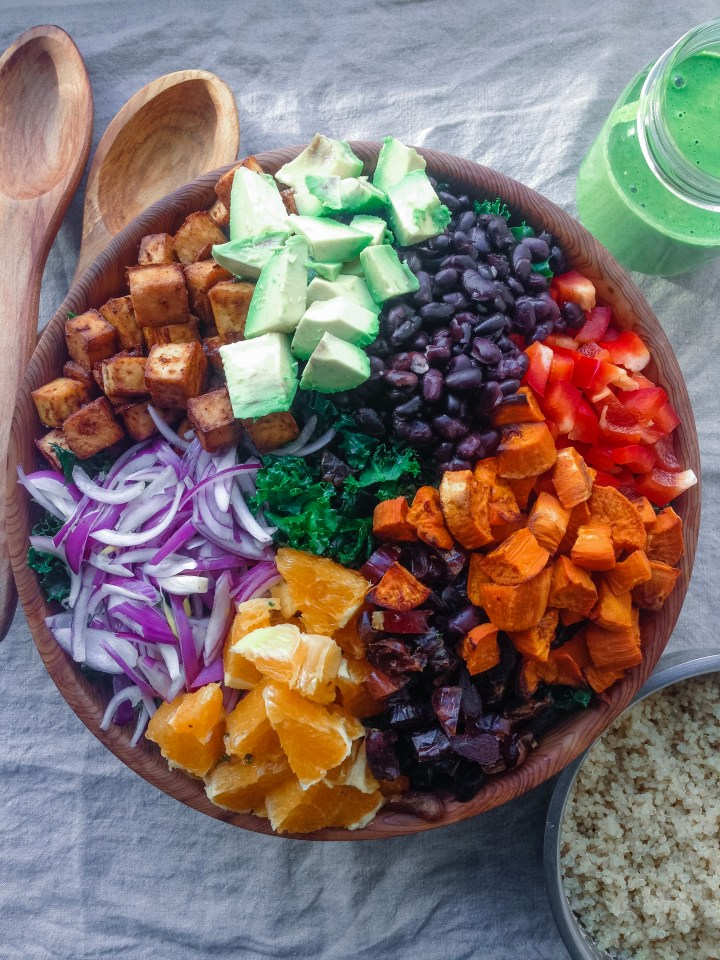 santa fe salad in a bowl made with sweet potato, dates, peppers, avocado, beans, crispy tofu, and creamy green cilantro dressing.