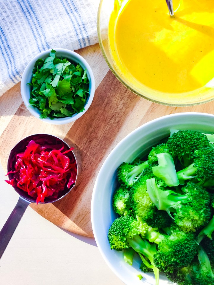 Components of a macrobiotic bowl: steamed broccoli, beet sauerkraut, cilantro, and turmeric tahini sauce