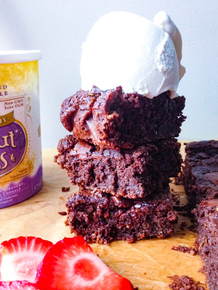 A stack of three oil-free brownies topped with a scoop of vanilla coconut ice cream.
