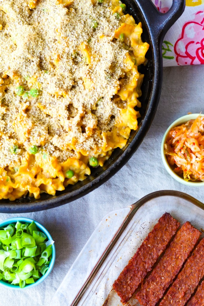 Nut Free Vegan Mac and Cheese with Tempeh Bacon in a skillet served with kimchi and green onion.