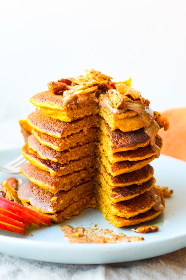 Pumpkin Spice Oatmeal Pancakes topped with almond butter and grain-free granola