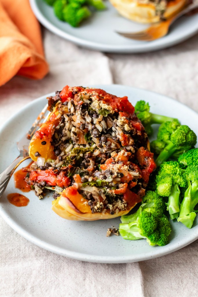 A serving of lentil and rice stuffed squash on a plate with steamed broccoli