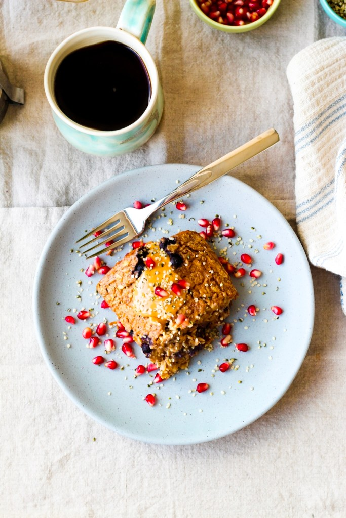 straight on shot of the peanut butter banana baked oatmeal on a plate with pomegranate arils and more peanut butter on top