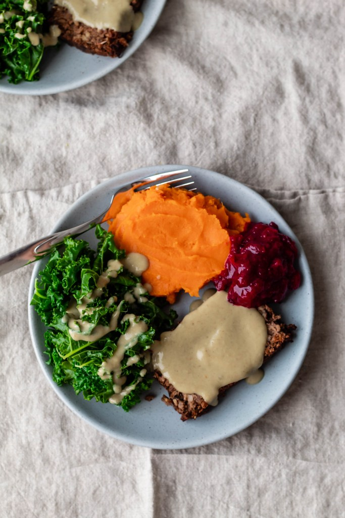 HOMEMADE 'BEYOND MEAT' MEATLOAF RECIPE on a plate surrounded by side dishes, miso gravy, and cranberry sauce