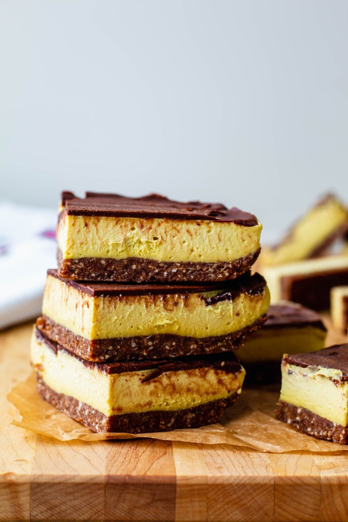 a stack of 3 nanaimo bars on a wooden cutting board