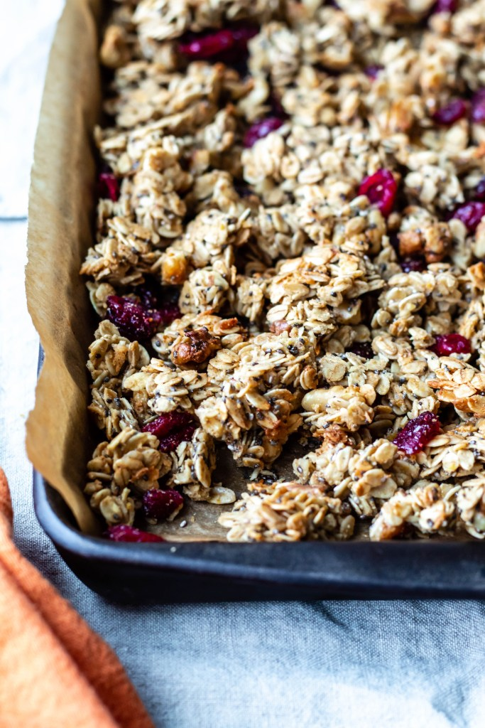 Cranberry, orange, and cardamom granola recipe. A healthy snack since it's sweetened with just a bit of maple syrup. Cozy and delicious.