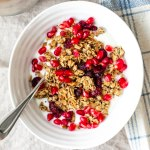 Cranberry, Orange, Cardamom Granola Recipe in a bowl of yogurt topped with pomegranate arils. Perfect healthy breakfast.