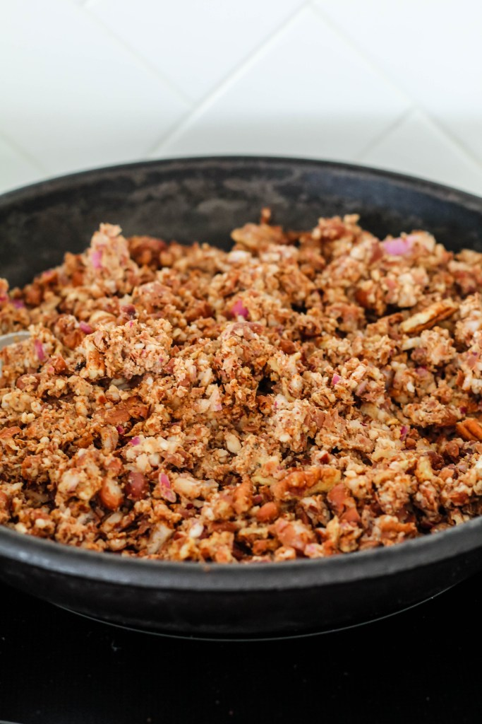 The pinto bean and pecan meat is shown in a cast iron skillet, being lightly cooked