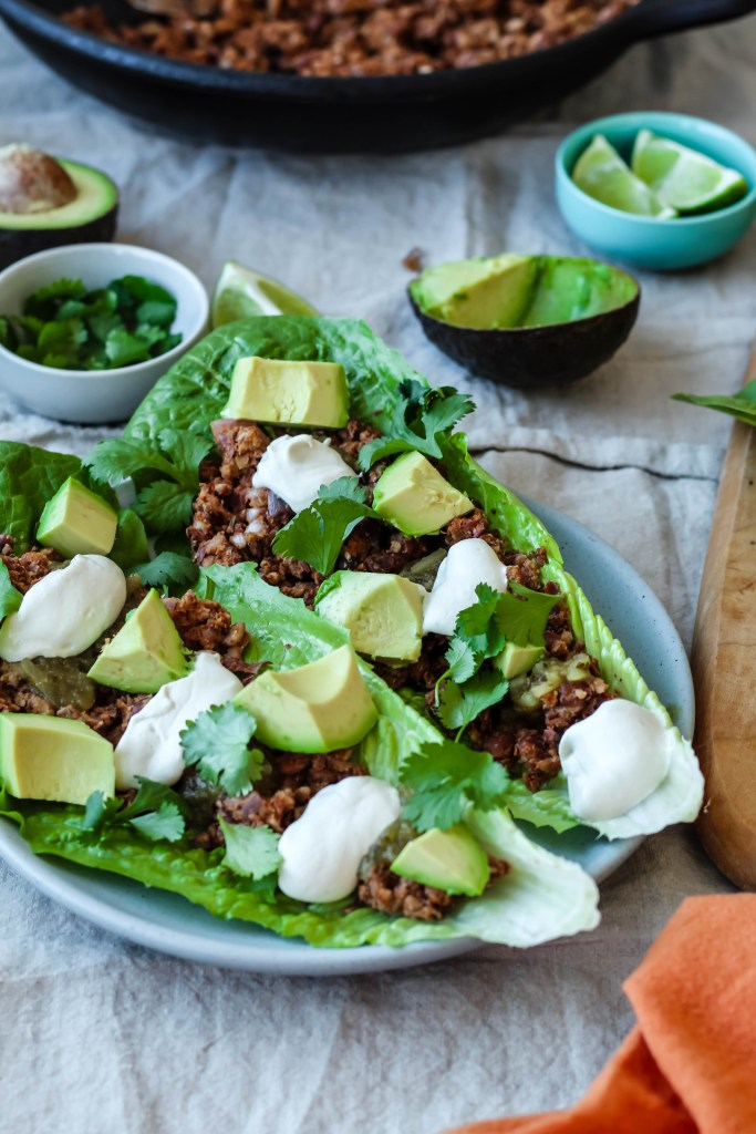 two pinto pecan lettuce tacos are shown on a plate surrounded by avocado, cilantro, and lime. They are topped with sunflower seed sour cream.