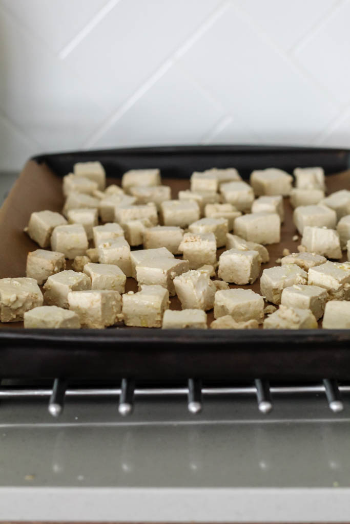 the tofu cubes are arranged on a baking sheet before going into the oven.