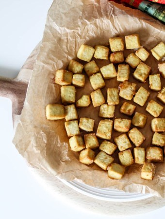an overhead shot of crispy baked tofu on a plate lined with parchment paper.