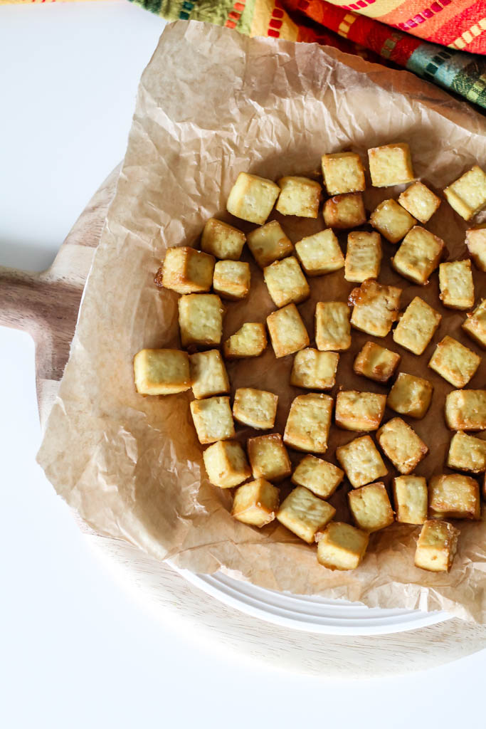 an overhead shot of crispy baked tofu on a sheet of crumpled parchment paper on a plate.