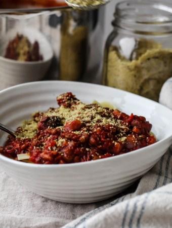 lentil walnut mushroom bolognese in a bowl sprinkled with sunflower seed parmesan