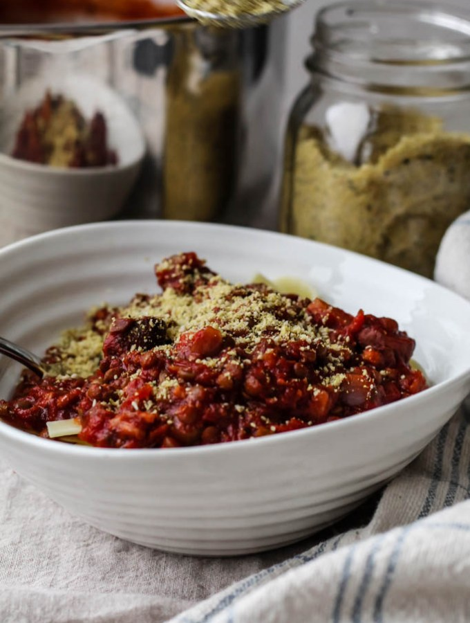 lentil walnut mushroom bolognese in a bowl sprinkled with sunflower seed parmesan
