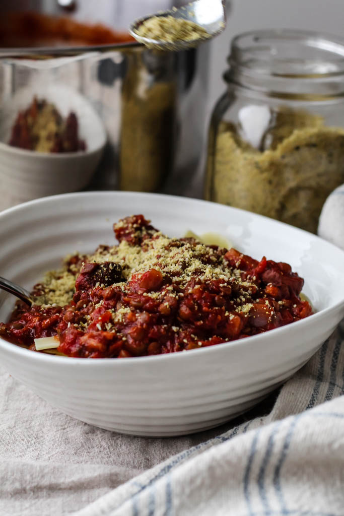 a bowl of the pasta topped with bolognese vegan pasta sauce sprinkled with sunflower seed parmesan.