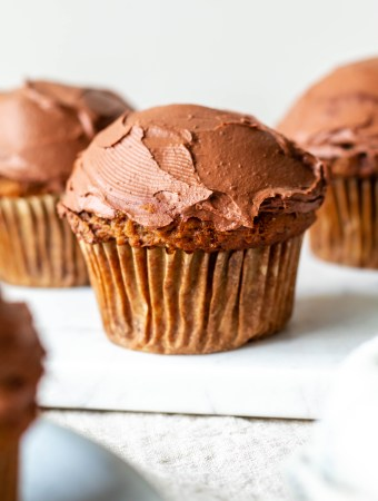 three banana spice cupcakes with chocolate frosting on a marble slab