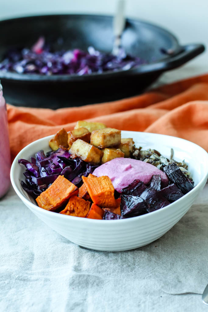 a straight-on shot of the winter buddha bowl showing detail on the beets, sweet potato, sunflower seed sauce, and cabbage.