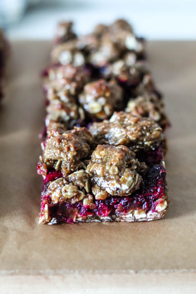 a head-on shot of a cranberry oatmeal square on a piece of parchment paper.