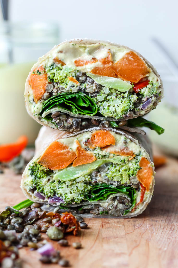 one mediterranean lentil veggie wrap sliced in half to show the fillings on a wooden cutting board with some of the lentils spilling out.