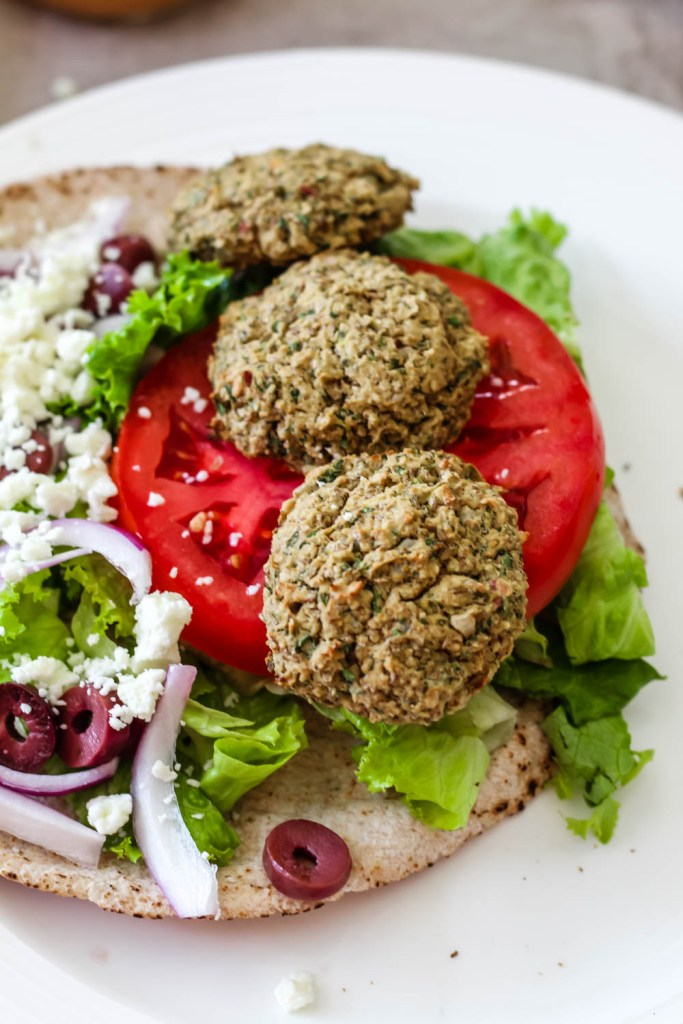 close up of the lentil falafels on a pita in the process of assembling the sandwiches