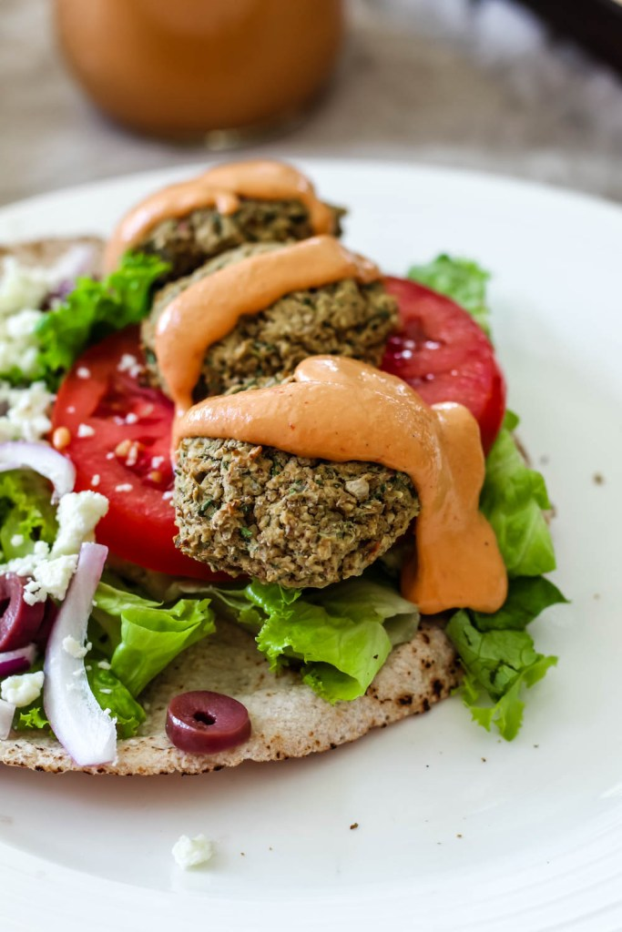 pita topped with lentil falafels, tomato, lettuce, red onion, olives, and chipotle tahini sauce