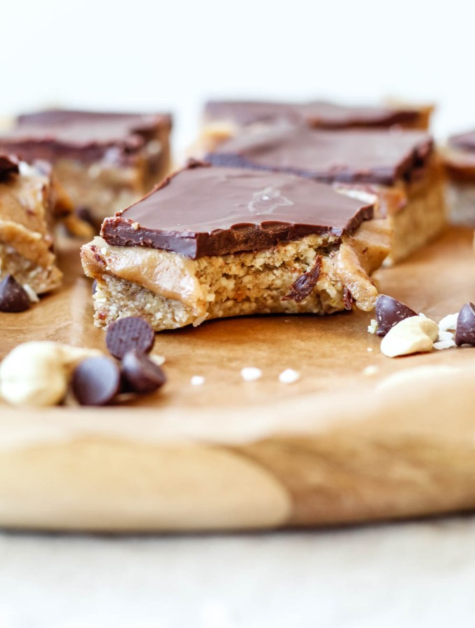 straight on shot of the triple layer caramel bars on a sheet of parchment