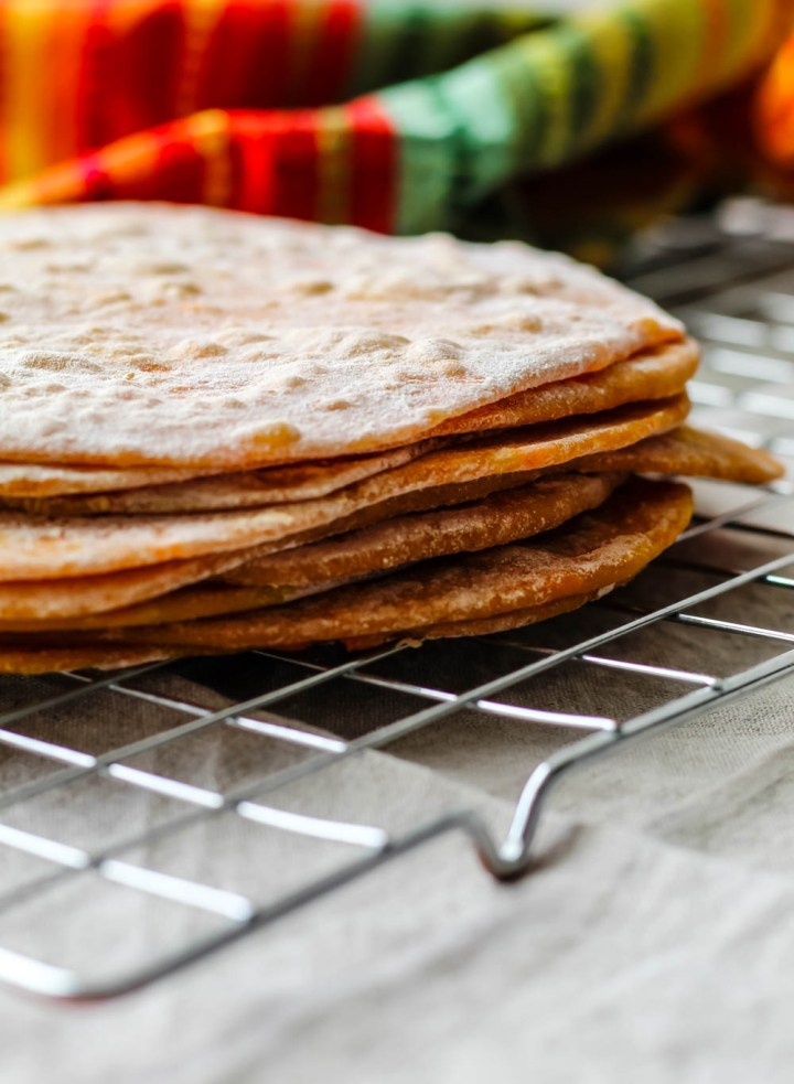 straight on shot of a stack of sweet potato spelt tortillas on wire cooling rack