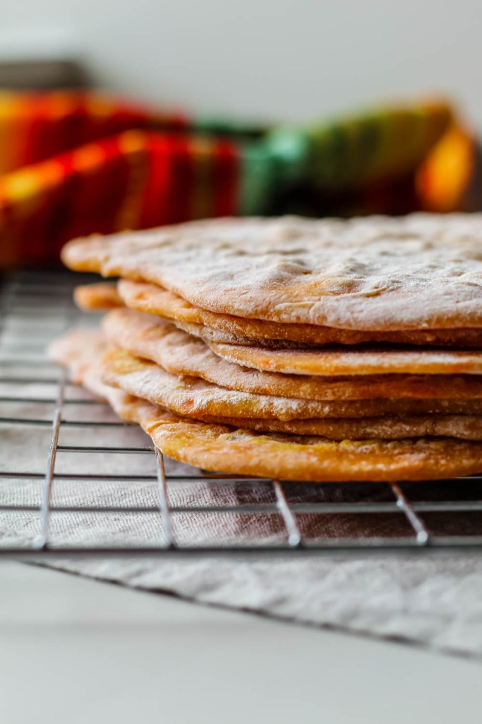 straight on shot of a stack of sweet potato spelt tortillas on a wire cooling rack