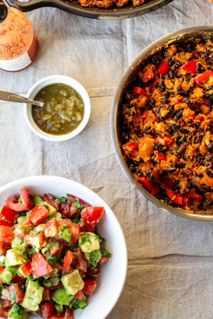 overhead shot of the sweet potatoes and black beans and the avocado salsa plus salsa verde in a dish