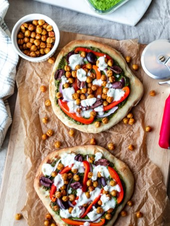 featured image for the post: two naan pesto pizzas on a wooden board