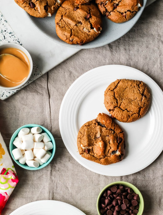 overhead shot of two vegan s'mores cookies on a plate with marshmallows, peanut butter, and chocolate chips in small dishes around them.