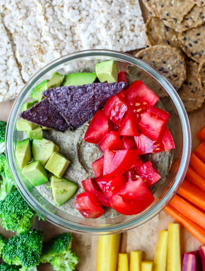 overhead shot of the black bean hummus topped with cubed avocado and tomato