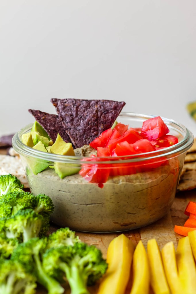 straight on shot of the dip in a glass container on a wooden board with raw veggies and crackers