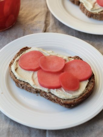 straight on shot of a slice of whole wheat bread topped with tofu cream cheese and pickled radishes