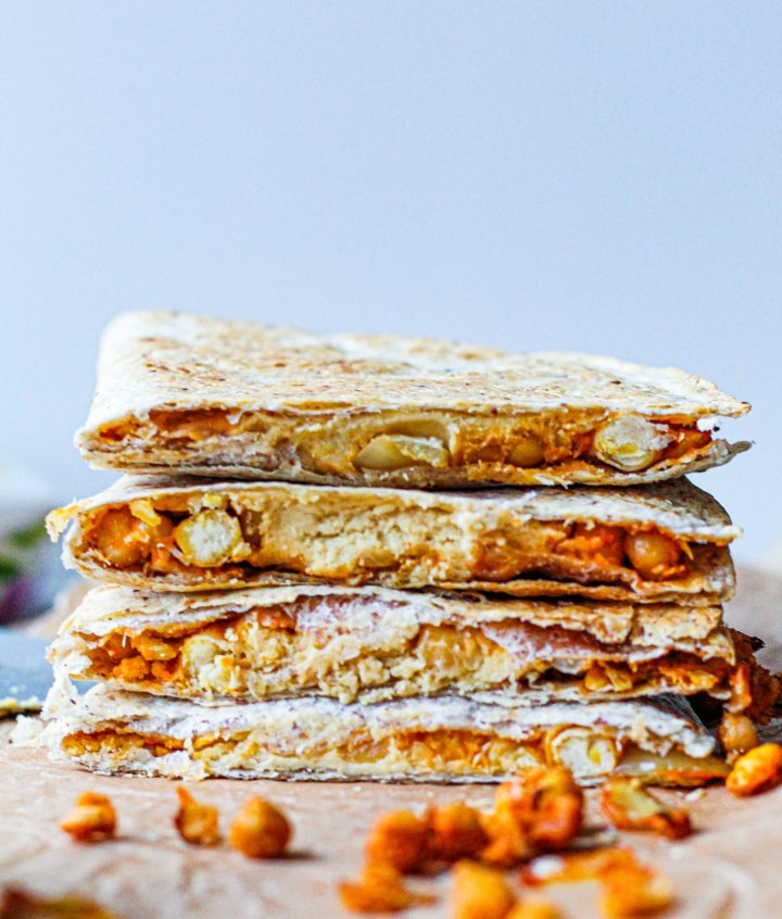 a shot of buffalo chickpea quesadilla slices stacked on top of each other showing the insides.