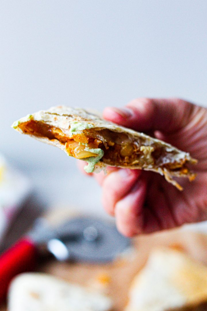 a triangle of quesadilla with a bite taken out of it
