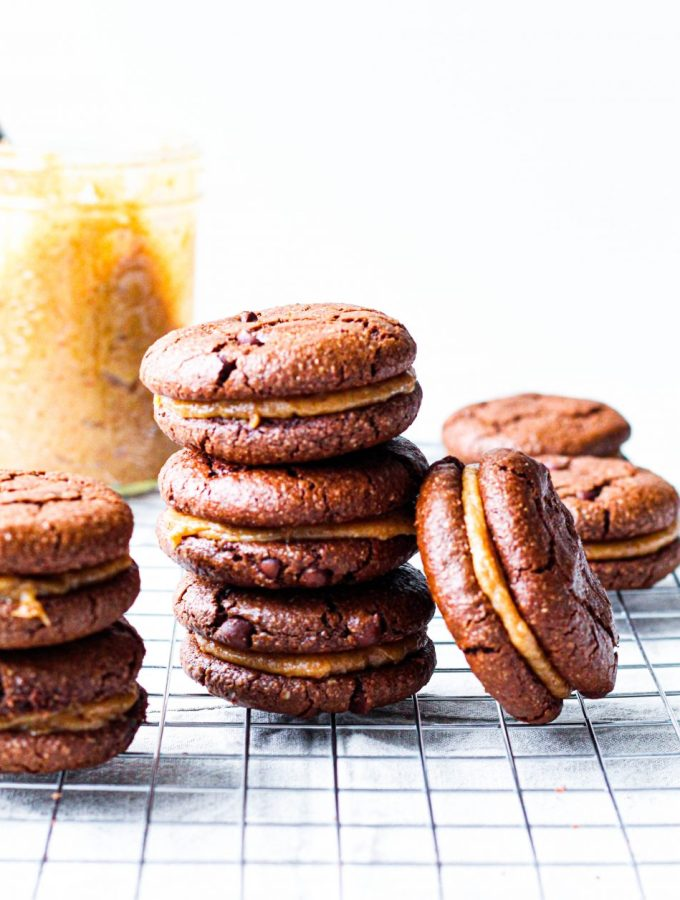 the featured image for the post, showing a stack of three sandwich cookies with a jar of date caramel in the background