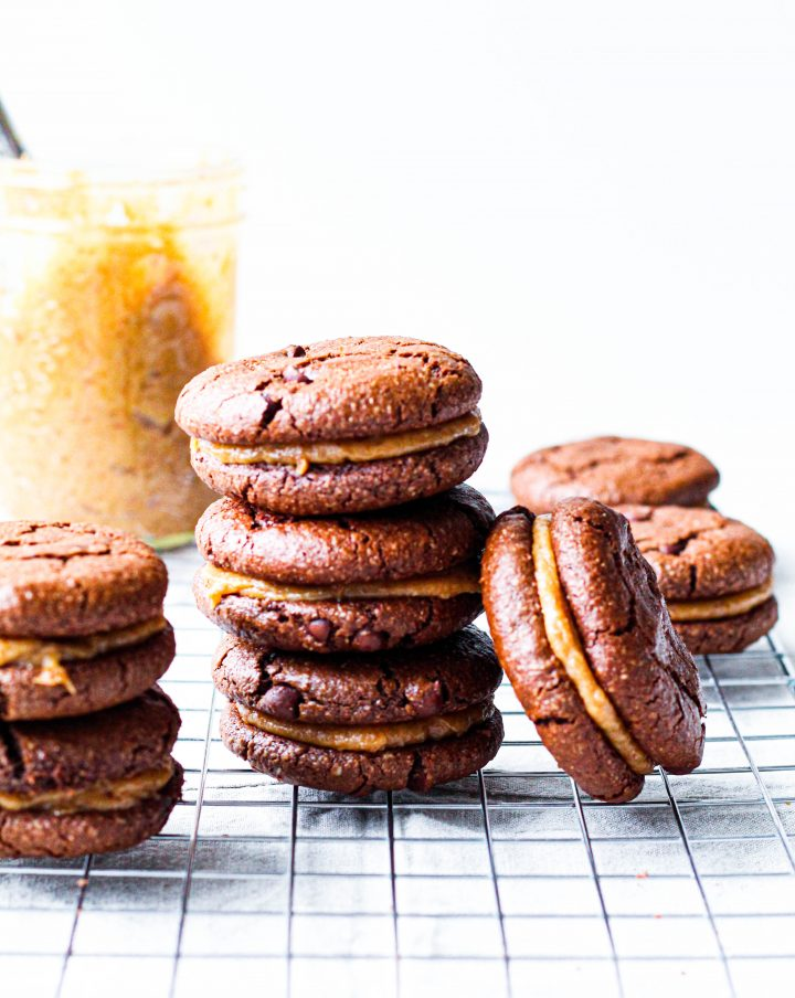 a stack of three of the vegan sandwich cookies is shown on a wire rack with a jar of the date caramel in the background.