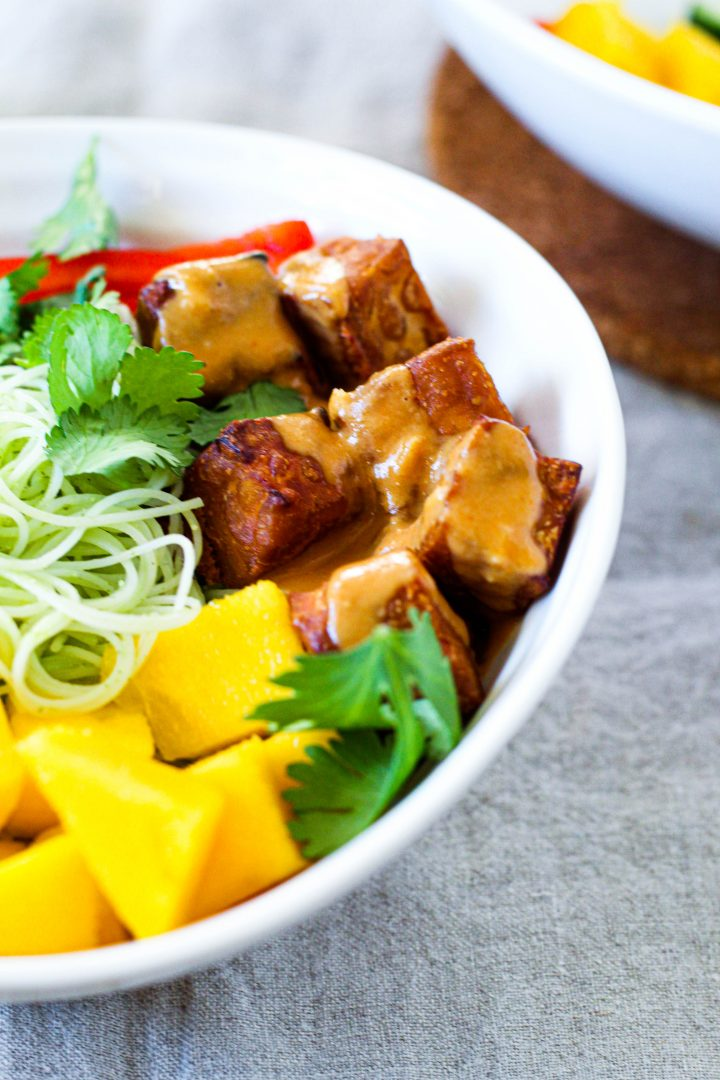 a straight on shot of an individual bowl of the salad with a close up on the peanut tempeh