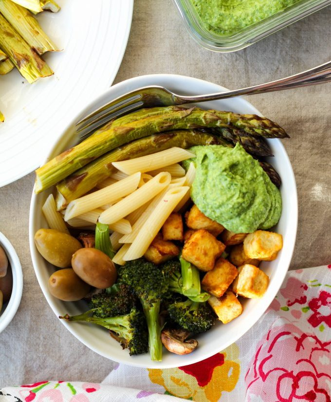 an overhead shot of the green goddess pesto bowl with pasta, tofu, green goddess pesto, roasted vegetables, and olives.